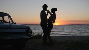 Het houdende van paar die op rivier` s kust dansen in zonsondergang, Reis van Minnaars op strandboulevard, danst jong paar aan Di stock videobeelden