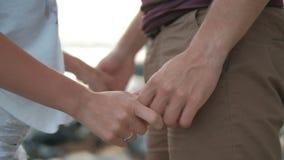 Het houdende van paar houdt handen en strijkt zacht in openlucht stock video