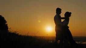 Het houdende van paar - moedige jonge mens en mooie meisjestribunes op hoge heuvel bij zonsondergang en heeft omhelzingen en de k stock videobeelden
