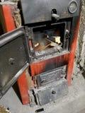 Het houten branden binnen de Stevige biobrandstofboiler Vernieuwbare energiebron groene milieuvriendelijke brandstof Oude warm stock afbeelding