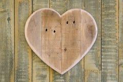 Het houten hart van liefdevalentijnskaarten op lichtgroene geschilderde achtergrond Stock Fotografie