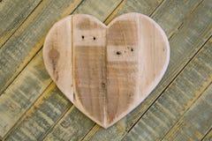 Het houten hart van liefdevalentijnskaarten op lichtgroene geschilderde achtergrond Stock Foto