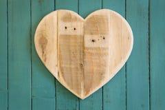 Het houten hart van liefdevalentijnskaarten op turkoois geschilderde achtergrond Stock Foto's