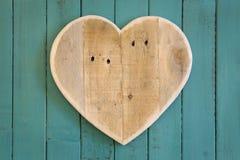 Het houten hart van liefdevalentijnskaarten op turkoois geschilderde achtergrond Royalty-vrije Stock Foto's
