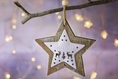 Het houten ornament van de Kerstmisster met rendieren die op droge boomtak hangen Het glanzen slinger gouden lichten Mooie achter Royalty-vrije Stock Foto's