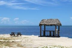 Het houten paviljoen en de bank op het strand en de blauwe hemel Stock Foto's