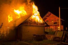 Het houten schuur branden bij nacht De hoge oranje brandvlammen, walm van onder betegeld dak op donkere hemel, bomensilhouetten e royalty-vrije stock afbeeldingen