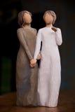 Het houten standbeeld van twee vrouwen die handen, standbeeld houden is op zwart m stock fotografie