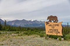 Het houten teken met gesneden draagt welkom heet bezoekers in Haines Junction stock fotografie