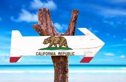 Het houten teken van Californië met strandachtergrond stock foto