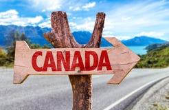 Het houten teken van Canada met een wegachtergrond Stock Fotografie