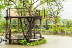 Het houten terras en de stoelen slingeren in de vijver tijdens regen stock afbeeldingen