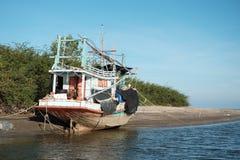 Het houten vissersbootanker op strand wordt klaar voor sleepnet rond Th Royalty-vrije Stock Foto's