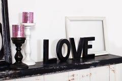 Het houten woord is liefde Op de open haard zijn twee kandelaars met kaarsen en de houten woordliefde Liefdeinschrijving in houte stock foto