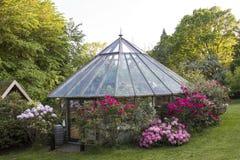 Het huis bouwt serre in een tuin stock afbeeldingen
