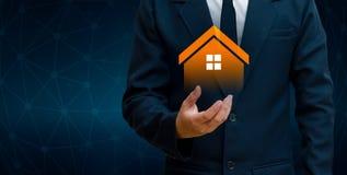Het huis is in de handen van het pictogram van het bedrijfsmensenhuis of het symboolconcept het huistoepassingen en toekomst van  Stock Afbeeldingen