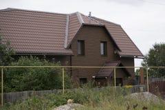 Het huis is in de schede gestoken in bruin hout stock foto's