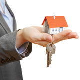 Het huis en de sleutels van de handholding Stock Foto's