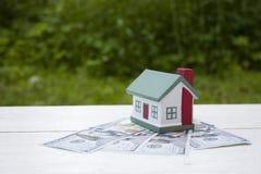 Het huis is honderd dollarsrekeningen waard Conceptuele foto stock afbeeldingen