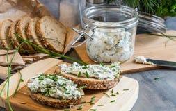 Het huis maakte brood op een houten scherpe raad met kwark en ricotta en kruiden Verfraaid met groene kruiden royalty-vrije stock fotografie