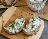 Het huis maakte brood op een houten scherpe raad met kwark en ricotta en kruiden Verfraaid met groene kruiden stock afbeeldingen