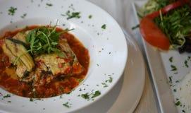 Het huis maakte voedselfotografie van een mediterrane fijngehakte die schotel van lamsmoussaka in een kom en een zijsalade wordt  stock foto's