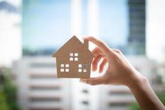 Het huis model, gelukkige huizen van de handholding voor families stock foto's