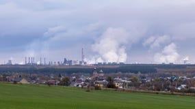 Het huis op de achtergrond van Rokende schoorstenen van de reusachtige fabriek stock foto's