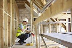 Het Huis van bouwvakkerusing drill on bouwt Stock Afbeeldingen