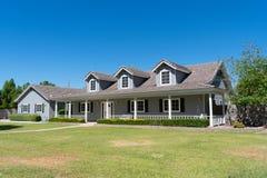 Het huis van de boerderijstijl met portiek en koekoeken royalty-vrije stock foto