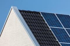 Het huis van de familie met verbonden zonnepanelen stock afbeeldingen