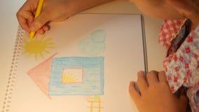 Het huis van de kindtekening, meisjeskleuring die, jonge geitjes ambacht, kinderenonderwijs 4K maken stock footage