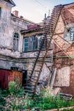Het huis van de laatste eeuw, de mening van de vensters van eerste verdieping en de brandtrap en de bloem tuinieren in binnenplaa royalty-vrije stock afbeelding