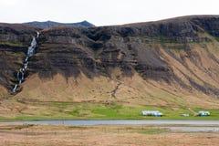 Het huis van de landbouwer bij de voet van de berg met een waterval royalty-vrije stock fotografie
