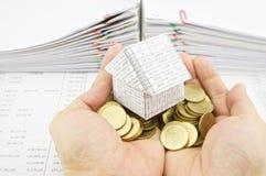 Het huis van de mensenholding op stapel gouden muntstukken over financiënrekening Royalty-vrije Stock Foto