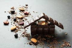 Het huis van de vakantiechocolade en droge vruchten met noten op een zwarte achtergrond stock foto