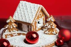 Het huis van de vakantiepeperkoek op rood Stock Foto's