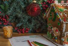 Het huis van het gemberbrood met Kerstboom en brief aan de Kerstman Stock Foto's