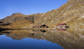 Het huis van het droommeer op berggebied stock foto