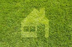 Het huis van het pictogram op groen gras Stock Afbeeldingen