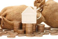 Het huis van het stuk speelgoed op zakken met muntstukken Stock Afbeelding