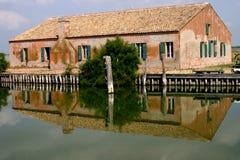 Het huis van vissers dat in het water wordt weerspiegeld Stock Fotografie