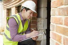 Het Huisbouw van architectenchecking insulation during royalty-vrije stock afbeelding