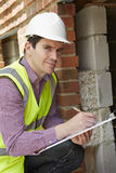 Het Huisbouw van architectenchecking insulation during royalty-vrije stock afbeeldingen