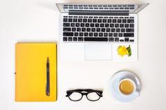 Het huisbureau van vrouwen Werkruimte met laptop, computer, geel notitieboekje, manierglazen, kop van koffie en geïsoleerde bloem royalty-vrije stock foto's