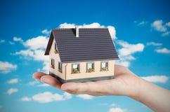 Het huisminiatuur van de handholding Het concept van huisfinanciën Royalty-vrije Stock Foto
