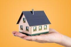 Het huisminiatuur van de handholding Het concept van huisfinanciën Royalty-vrije Stock Foto's