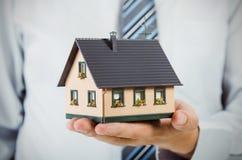 Het huisminiatuur van de makelaar in onroerend goedholding Het concept van huisfinanciën Royalty-vrije Stock Fotografie