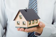 Het huisminiatuur van de makelaar in onroerend goedholding Het concept van huisfinanciën Stock Foto's