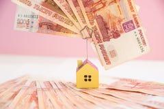 Het huismodel plaatste op bankbiljet voor de financiën van het de hypotheekfonds van de concepteninvestering en huislening Klein  stock afbeeldingen